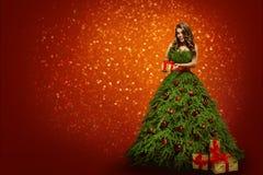 Femme dans la robe d'arbre de Noël tenant le cadeau actuel, fille de mode image stock