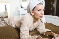 Femme dans la robe de chambre ayant la serviette sur la t?te et le livre de lecture image stock