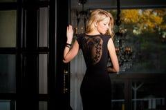 Femme dans la robe de cocktail se tenant dans un couloir Image stock