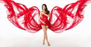 Femme dans la robe de ondulation de vol rouge comme ailes images libres de droits