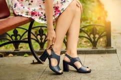 Femme dans la robe du pied dans les chaussures de la douleur de rue de banc dans les jambes image stock