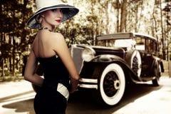 Femme dans la robe intéressante et le chapeau contre le rétro véhicule image stock