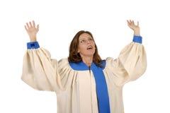 Femme dans la robe longue de choeur félicitant Dieu Photographie stock