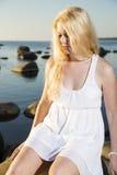 Femme dans la robe prenant le soleil sur la pierre images stock