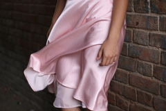 Femme dans la robe rose avec la jupe se soulevante, supports près du mur de briques Photos stock