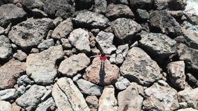 Femme dans la robe rouge avec des mains se tenant à part sur le tir aérien de vue supérieure de roches Bourdon tiré de la dame da banque de vidéos