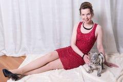 Femme dans la robe rouge avec le chien sur la couverture Photographie stock