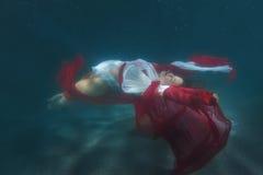 Femme dans la robe rouge dansant sous l'eau photo stock