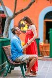 Femme dans la robe rouge se tenant vis-à-vis de l'ami outside Photographie stock