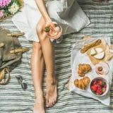 Femme dans la robe se reposant avec du vin et des casse-croûte, culture carrée Image stock