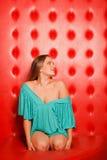 Femme dans la robe se reposant sur le divan en cuir Photographie stock libre de droits