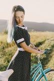 Femme dans la robe se tenant avec la bicyclette Photo libre de droits