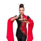 Femme dans la robe traditionnelle avec des sushi, d'isolement Image stock