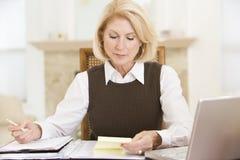 Femme dans la salle à manger avec l'ordinateur portatif et les écritures Photo libre de droits