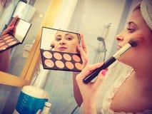 Femme dans la salle de bains appliquant le bronzer de découpe sur la brosse images libres de droits