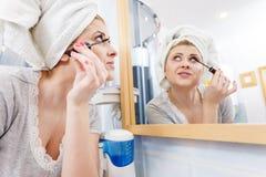 Femme dans la salle de bains appliquant le mascara sur des cils Photos libres de droits