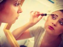 Femme dans la salle de bains appliquant le mascara sur des cils image libre de droits