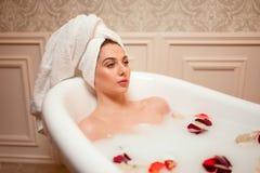 Femme dans la salle de bains avec des pétales de rose Photographie stock libre de droits