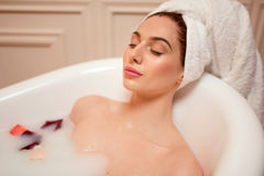 Femme dans la salle de bains avec des pétales de rose Photo stock