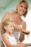 Femme dans la salle de bains balayant le cheveu de jeune fille Photographie stock libre de droits
