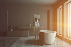 Femme dans la salle de bains grise avec le baquet et l'évier photographie stock libre de droits