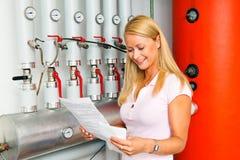 Femme dans la salle de chaudière pour le chauffage. image libre de droits