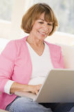 Femme dans la salle de séjour avec le sourire d'ordinateur portatif photographie stock libre de droits