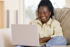 Femme dans la salle de séjour utilisant l'ordinateur portatif Photos libres de droits