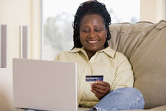 Femme dans la salle de séjour utilisant l'ordinateur portatif Photos stock