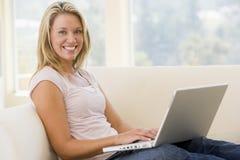 Femme dans la salle de séjour utilisant le sourire d'ordinateur portatif Image libre de droits
