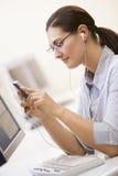 Femme dans la salle des ordinateurs écoutant le joueur MP3 Photo stock
