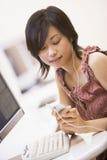 Femme dans la salle des ordinateurs écoutant le joueur MP3 Photos libres de droits