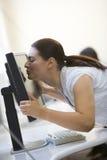 Femme dans la salle des ordinateurs embrassant le moniteur Photos libres de droits