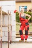 Femme dans la salopette travaillant au chantier de construction photographie stock