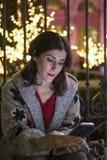 Femme dans la scène de Noël de nuit regardant l'écran de smartphone Images stock