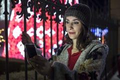 Femme dans la scène de Noël de nuit regardant l'écran de smartphone Image libre de droits