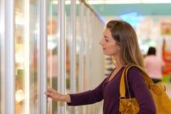 Femme dans la section de congélateur de supermarché Photo stock