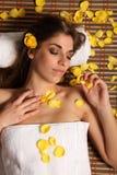 Femme dans la station thermale de santé détendant avec des pétales de fleur Image stock