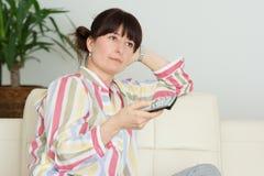 Femme dans la télévision de observation à la maison image stock