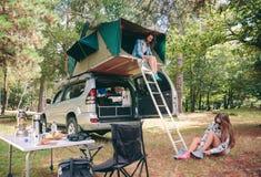 Femme dans la tente au-dessus de 4x4 et autre mettant la hausse Photographie stock libre de droits