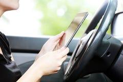 Femme dans la voiture avec le PC de comprimé Photographie stock