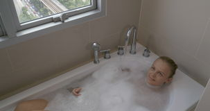 Femme dans le bain détendant de la grande ville Vue de fenêtre vers Bangkok, Thaïlande banque de vidéos