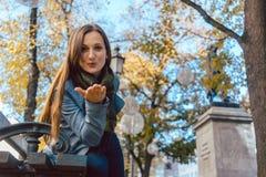 Femme dans le baiser de soufflement d'amour en parc d'automne Image libre de droits