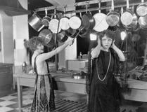 Femme dans le battement de cuisine sur des pots et casseroles (toutes les personnes représentées ne sont pas plus long vivantes e Image stock