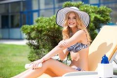 Femme dans le bikini appliquant la crème de bloc du soleil sur bronzée photographie stock