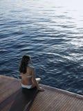 Femme dans le bikini détendant sur la planche du yacht Images libres de droits