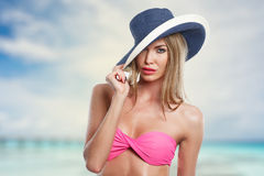 Femme dans le bikini et le chapeau sur la plage Photo stock