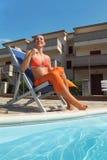 Femme dans le bikini et pareo se reposant sur la présidence de plage photo stock