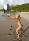 Femme dans le bikini jouant avec le beachball sur la plage Photographie stock libre de droits