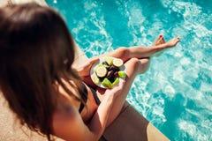 Femme dans le bikini mangeant des fruits et détendant dans la piscine Tout inclus Vacances d'été images libres de droits